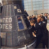 JFK looks at the space craft , the spacecraft that made three earth orbits, piloted by astronaut .