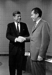 Kennedy shakes Richard Nixon's hand before a televised debate.