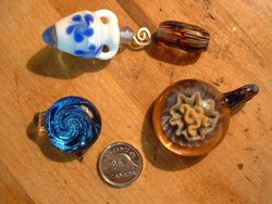 Hand-blown glass beads and pendants illustrate some of the myriad colors and shapes of glass art (The   is for .)