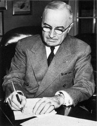 President Truman signing a proclamation declaring a national emergency that initiates U.S. involvement in the Korean War.