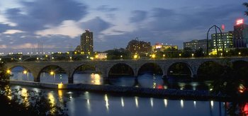 Minneapolis at dusk, featuring the Stone Arch Bridge and the flour mills that were part of the city's initial economy.