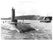 HMS Conqueror returning to port flying the
